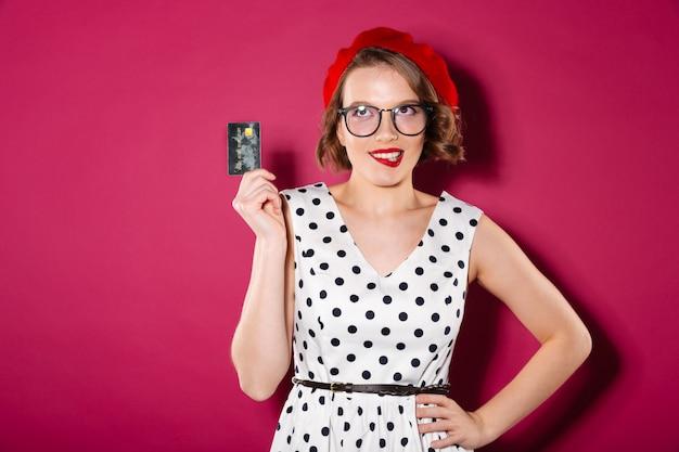 Заинтригованная рыжая женщина в платье и очках с рукой на бедре держит кредитную карту, прикусывает губу и смотрит на розовый