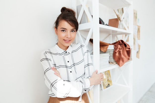 立っている若い笑顔の女性ファッション・デザイナー