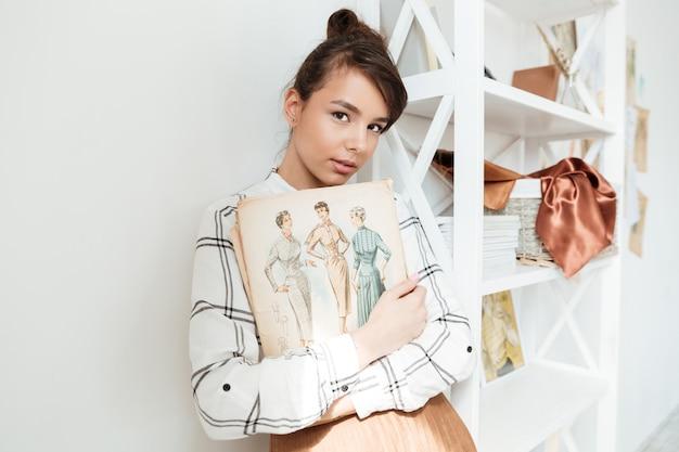 スケッチブックを保持している若い女性ファッション・デザイナー