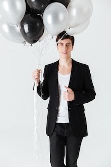 Вертикальное изображение улыбающегося человека, держащего воздушные шары