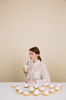 集中している若い女性がコーヒーを保持しているカップケーキに近いポーズ