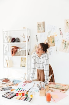 彼女の仕事机にもたれて笑顔のプロの女性デザイナー