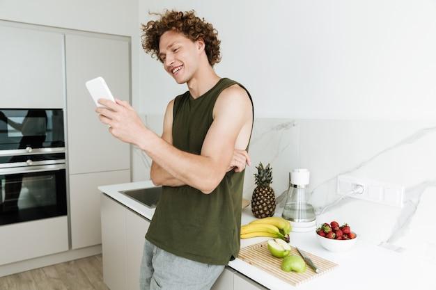 Мужчина стоит на кухне и болтает по телефону