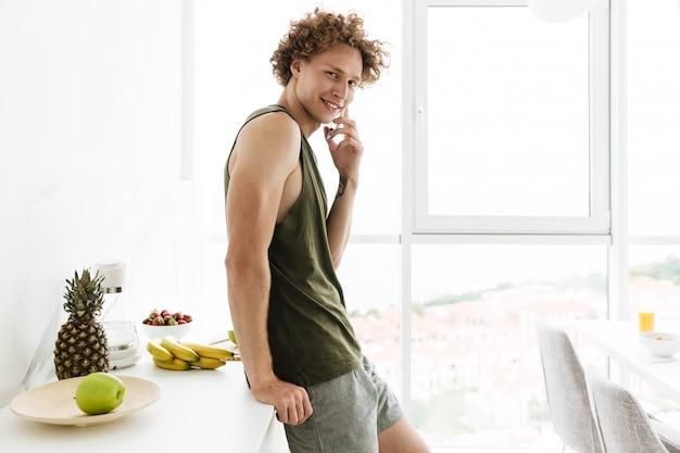Веселый человек стоит на кухне и разговаривает по телефону