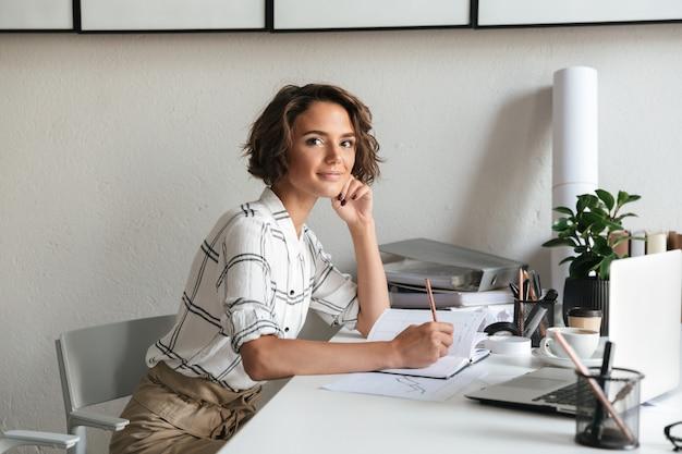 Вид сбоку удивительной женщины, сидящей за столом