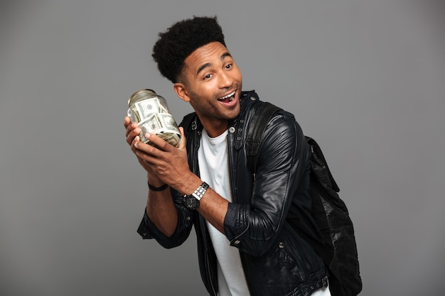 よそ見、お金で銀行を保持している革のジャケットでハンサムな幸せなアフロアメリカン男