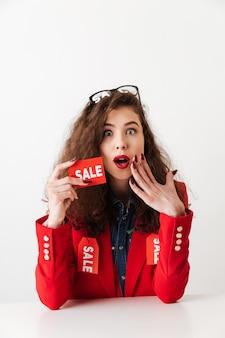 Торговый женщина, держащая продажи знак, сидя за столом