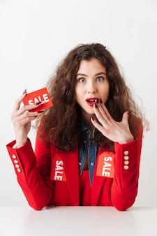 Удивленная шопоголика женщина, держащая продажи знак