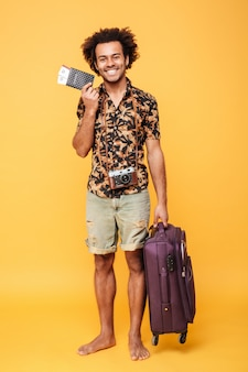 パスポートとスーツケースを持って幸せなアフリカ人。