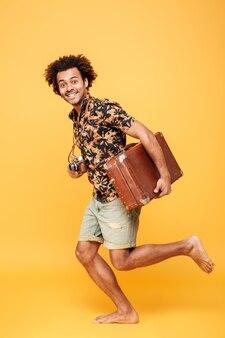 スーツケースを持って走っている若い幸せなアフリカ人