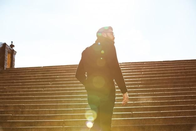 屋外の階段の上を歩く男の背面図