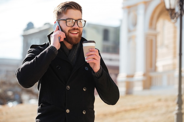 携帯電話で話していると、コーヒーを飲みながら幸せな若い男