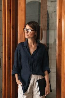 ガラスのドアの近くに立っている手でフォルダーを持つ眼鏡のビジネス女性の垂直方向の画像