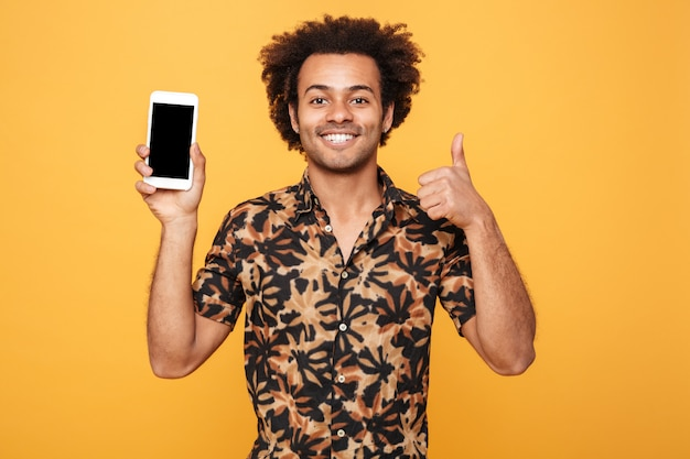 空白の画面の携帯電話を示す陽気な若いアフロアメリカンの男