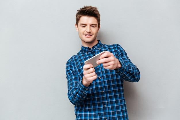 Молодой человек, играя в игры на смартфоне