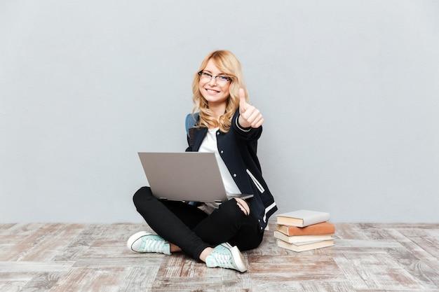 Счастливый студент молодой женщины используя портативный компьютер.