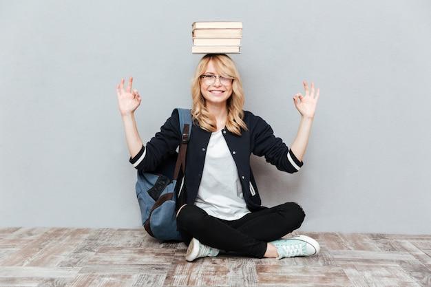 Счастливый студент молодой женщины держа книги на голове.