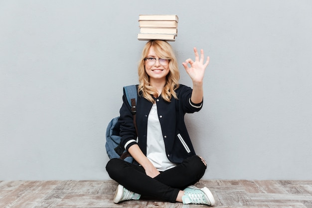 陽気な若い女性学生の頭の上の本を保持しています。
