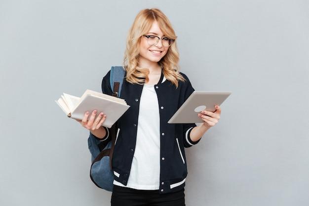 タブレットと本を持つ学生