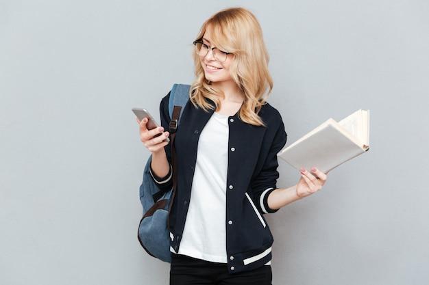 電話と本を持っている学生