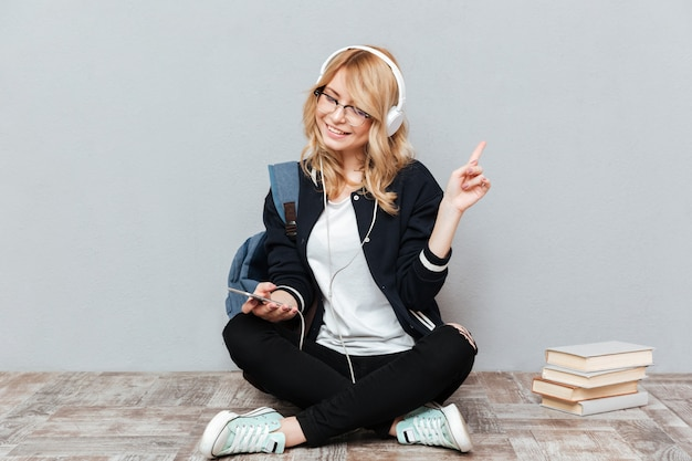 幸せな女子学生が床で音楽を聴く