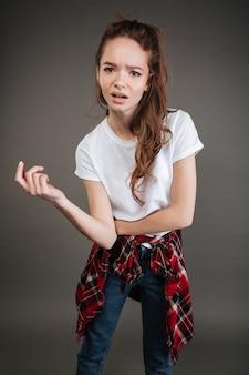 混乱している若い女性が灰色の壁に孤立したポーズ