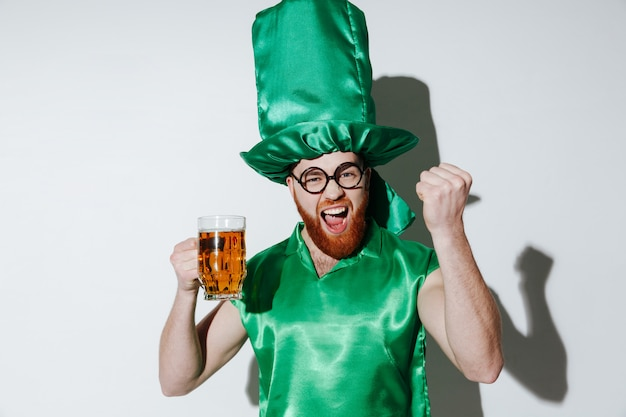 ビールを保持しているセントパトリックス衣装で幸せな男