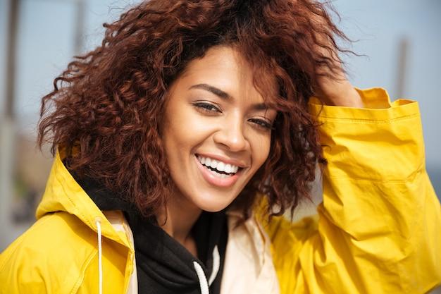 黄色のコートを着て幸せなアフリカの巻き毛の若い女性