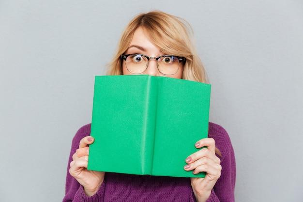 本で顔を隠す女