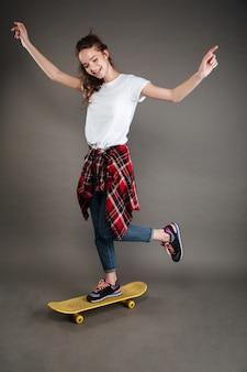 スケートボードに乗って幸せな屈託のない少女の完全な長さ