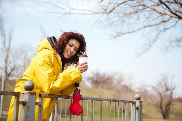 コーヒーを飲みながら野外を歩いている黄色いコートを着ている陽気なアフリカの巻き毛の若い女性の写真。