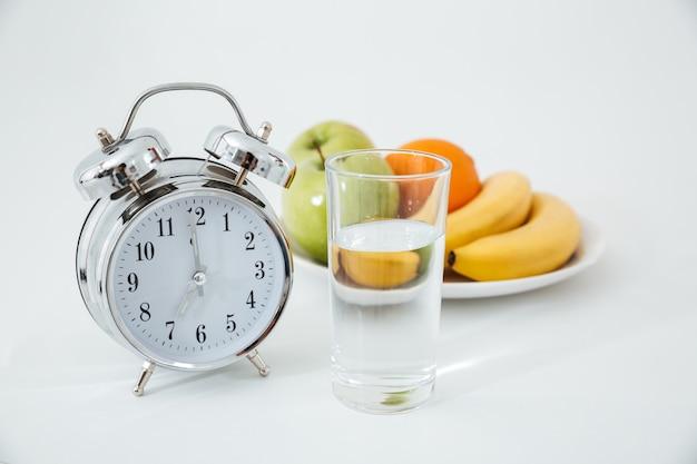 アラームと果物の近くの水のグラス