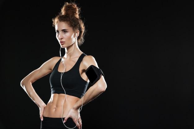 Спокойная фитнес женщина, держащая руки на бедрах