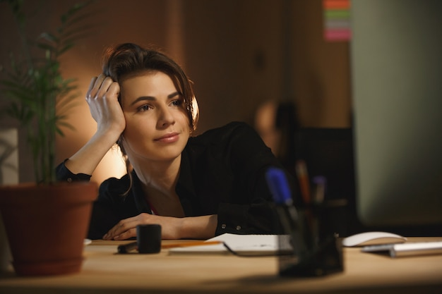 夜のオフィスに座っている若い女性デザイナーを集中