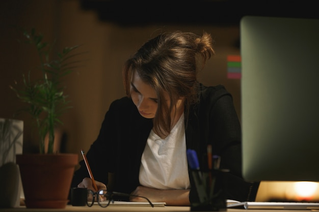 Концентрированный молодой леди дизайнер сидит в офисе