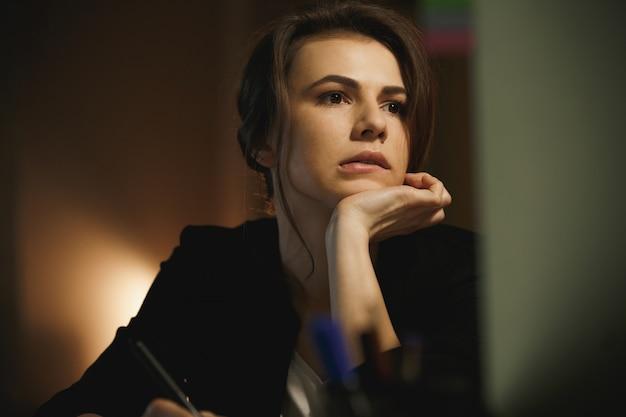 Серьезный молодой леди дизайнер сидит в офисе ночью