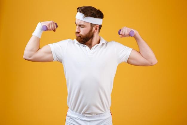Серьезный ретро спортсмен с легкими гантелями
