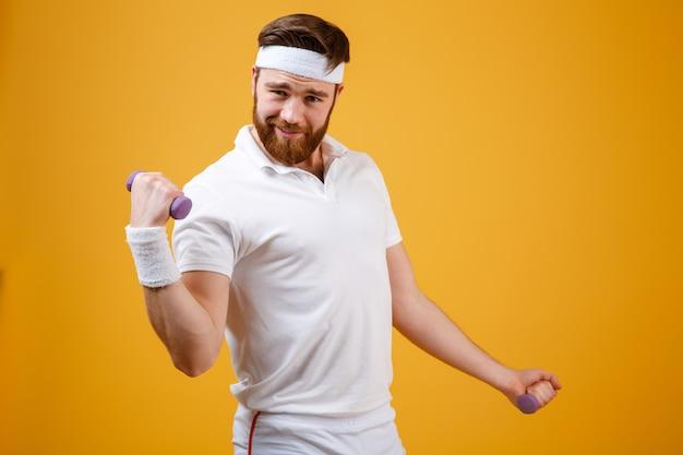 Смешной спортсмен делает упражнения с легкими гантелями
