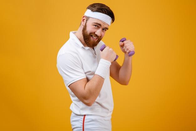 Спортсмен стоит боком, держа легкие гантели