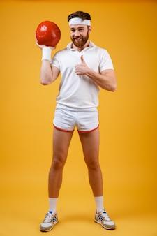 ボールを保持している陽気な若いスポーツマンは親指ジェスチャーを作る