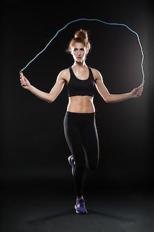 縄跳びでジャンプするフィットネス女性の全身写真