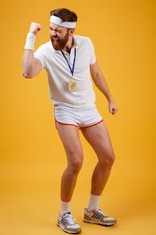 メダルを持つ感情的な若いスポーツマンは、勝者のジェスチャーを作ります。