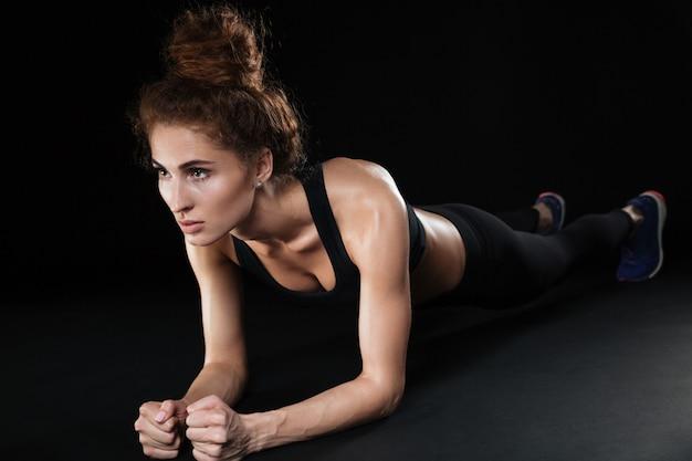 フィットネス女性は板の運動をする