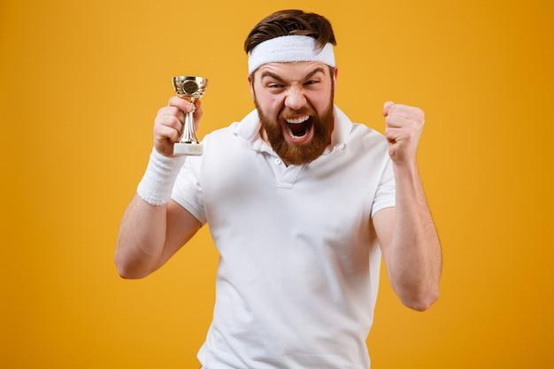 報酬を保持している感情的な若いスポーツマンは勝者のジェスチャーを作ります。