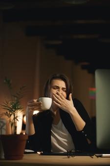 屋内で座っているあくびの若い女性デザイナー