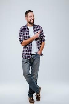 Полная длина портрет бородатый мужчина в рубашке, указывая в сторону