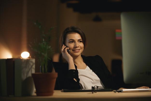 Счастливый дизайнер молодой женщины разговаривает по телефону