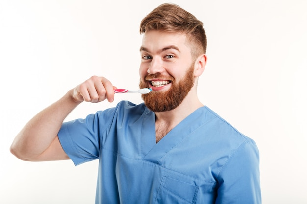 Портрет молодого дантиста учит пациента чистить зубы