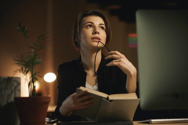 Концентрированный молодой леди дизайнер чтение книги.