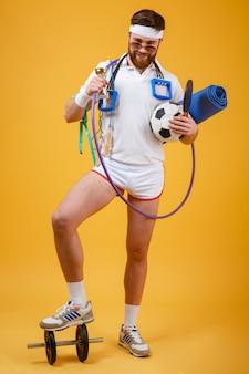ゴールデンカップとスポーツ用品を保持している満足して幸せな男のチャンピオン
